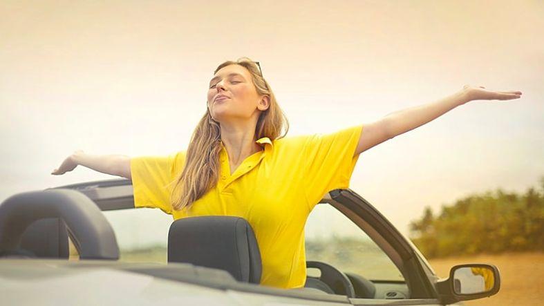 mulher de braços apertos e um carro conversível