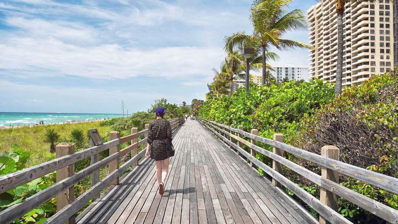 mulher caminhando ao lado da praia - Happy Tours