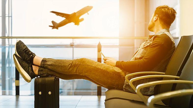 homem sentado no aeroporto olhando o avião da janela